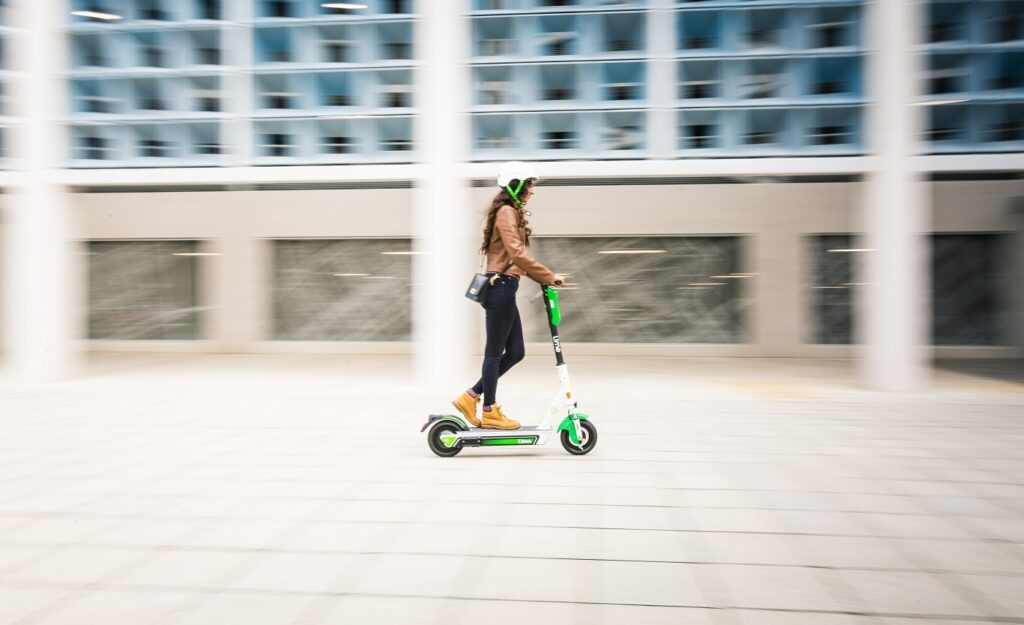 Ellie rides a Lime electric scooter at speed